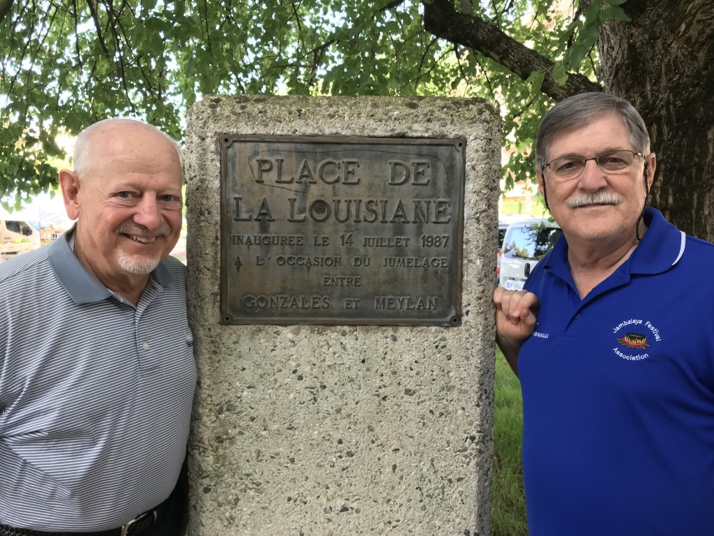 "Councilman Cagnolatti & Mayor Arceneaux by the plaque commemorating the twinning of Meylan and Gonzales and naming the park ""Louisiana Plaza"". They have a farmer's market every morning in this plaza. There is a clothing vendor, flower vendor, cheese vendors, food truck, bread vendor, sausage vendor, and several vegetable vendors."